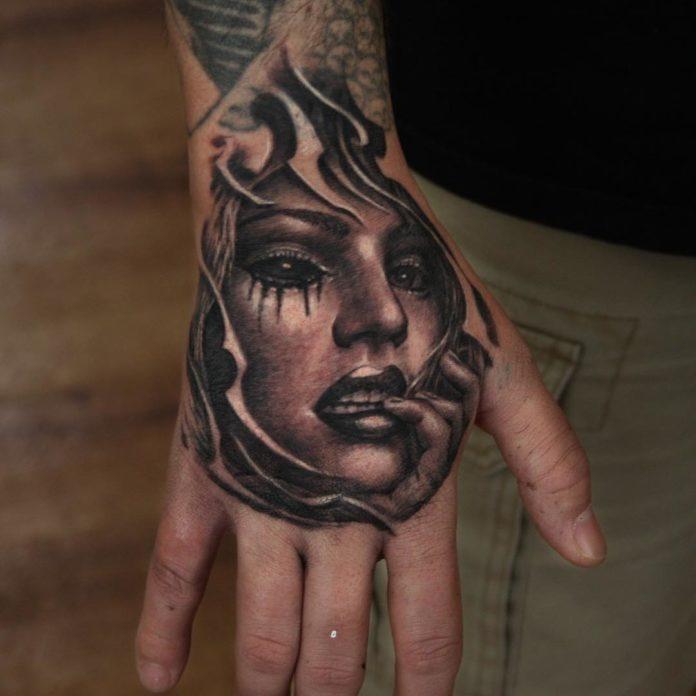 Tatouage de femme avec un œil en sang tenant la joue