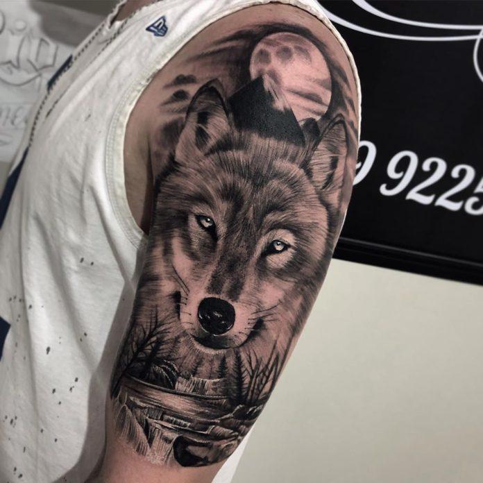 Tatouage d'un beau Loup décoré d'une rivière et des montagnes sur l'épaule