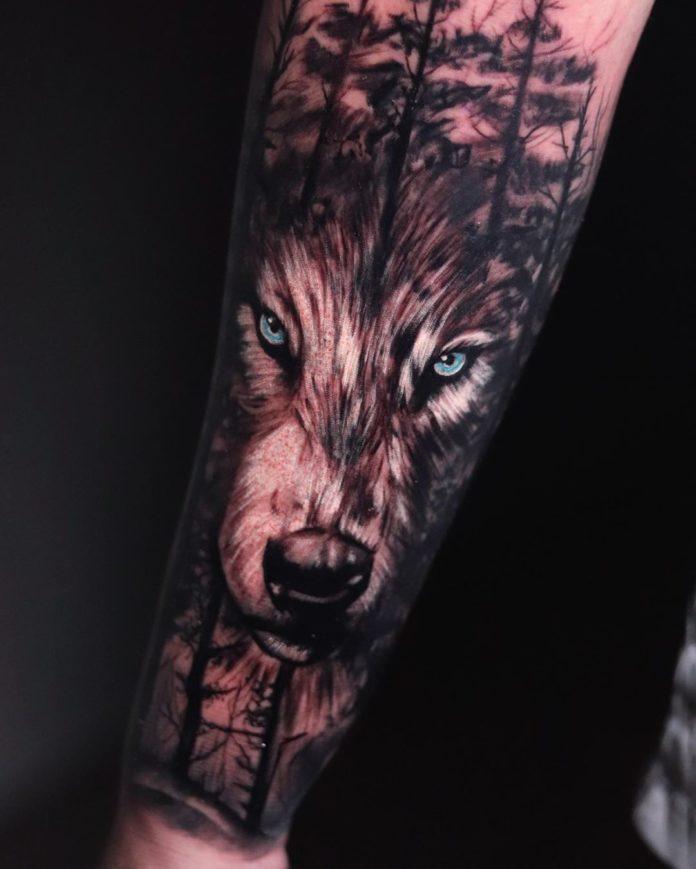Tatouage de visage de Loup aux yeux bleus dans la forêt sur avant bras