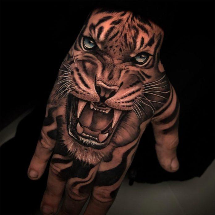 Tatouage réaliste de tête de tigre aux yeux bleus rugissant