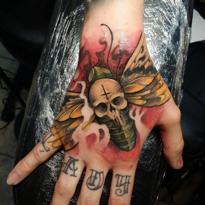 Tatouage d'un papillon avec une tête de mort sur le dos