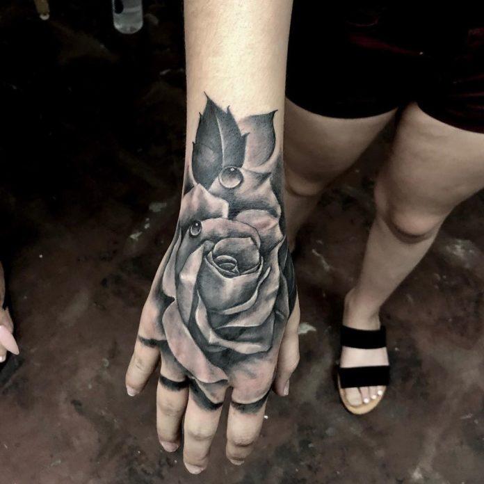 Tatoo en noir et blanc d'une rose avec des gouttes d'eau