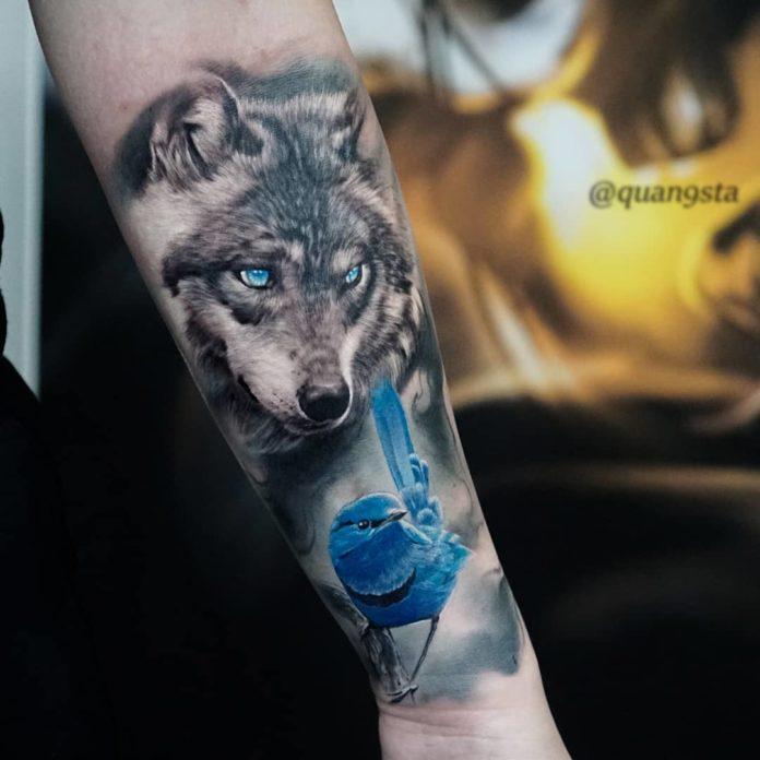 Tatouage de tête de Loup avec un oiseau bleu sur avant bras