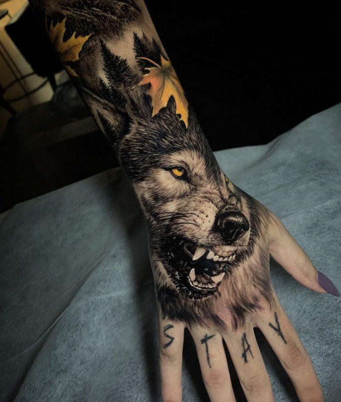 Tatouage de loup montrant ses crocs avec un mot gravé sur les doigts
