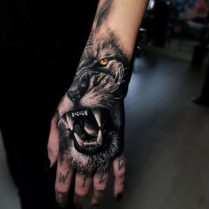 Tatouage de moitié visage de lion rugissant avec un mot sur les doigts