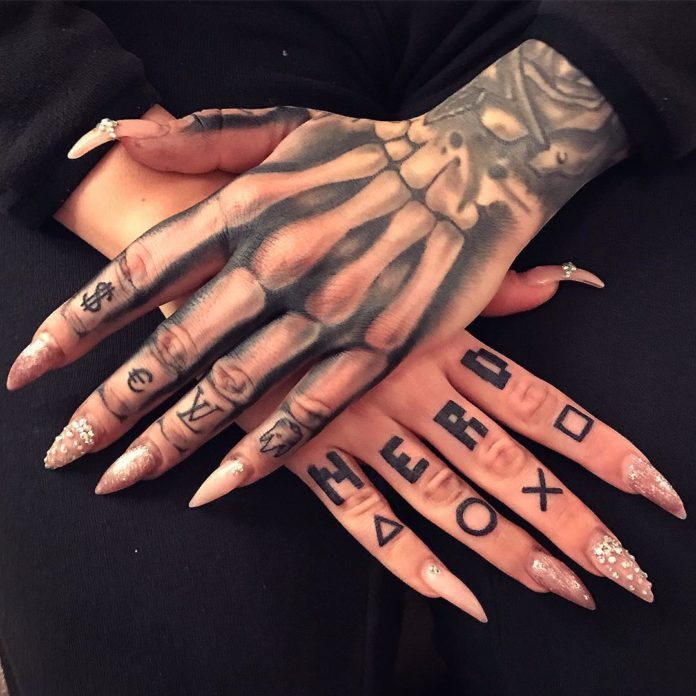 Tatouage squelette de main avec des lettres sur chaque doigt