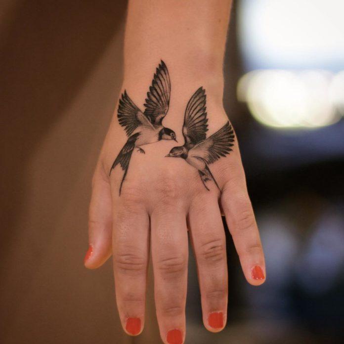 Tatouage d'hirondelle sur la main