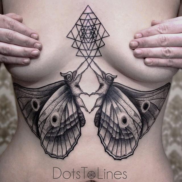 Tatouage artistique de deux papillons avec une forme géometrique